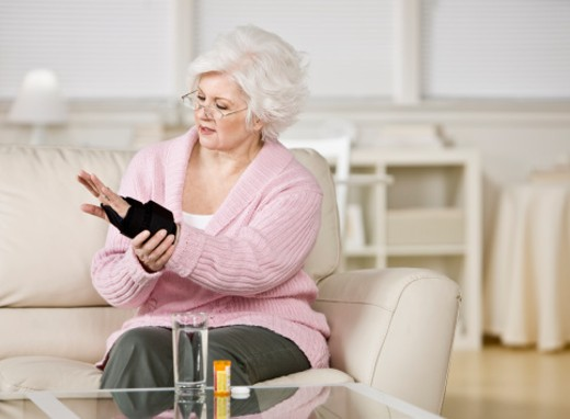 Senior woman taking medication for hurt wrist in living room : Stock Photo