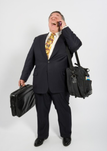 Senior business man with luggage laughing on mobile phone, studio shot : Stock Photo