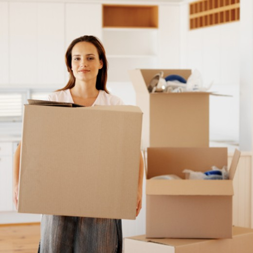 Stock Photo: 1491R-1153427 portrait of a young woman carrying a cardboard box