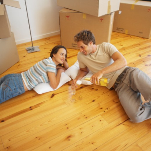 young couple lying on the floor drinking champagne : Stock Photo