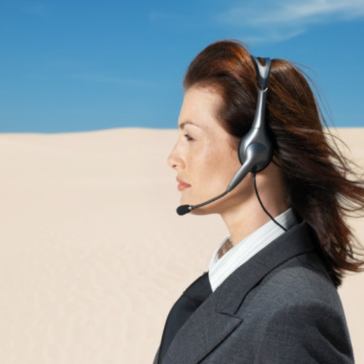 side profile of a young woman wearing a headset standing in the desert : Stock Photo