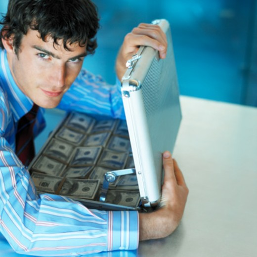 portrait of a businessman holding an open briefcase full of money : Stock Photo