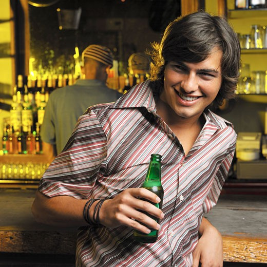 Stock Photo: 1491R-1154300 portrait of a young man standing at the bar holding a beer