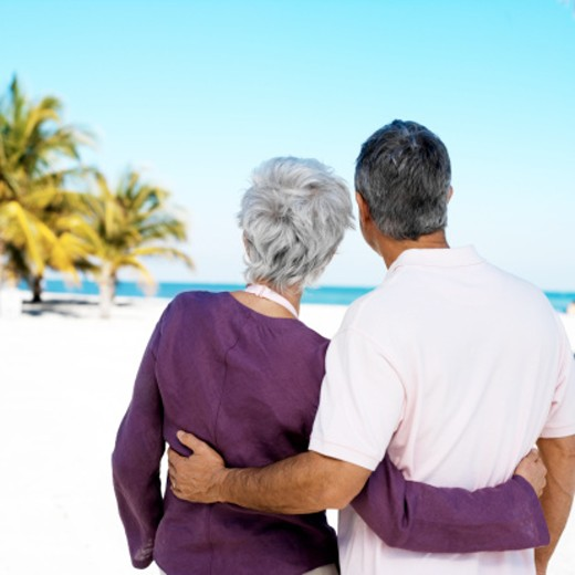 Stock Photo: 1491R-1154615 back of a mature couple admiring the view of the beach