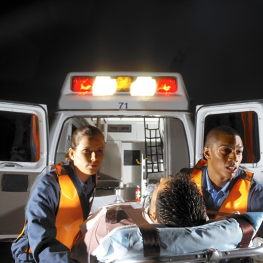 Stock Photo: 1491R-1154797 paramedics rushing a patient to the ambulance