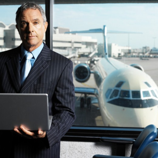 portrait of a businessman standing by airport window holding laptop : Stock Photo