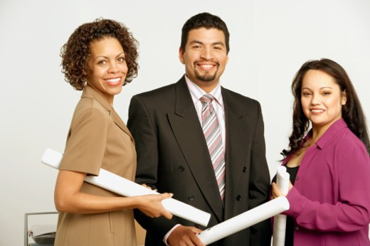 Portrait of a businessman and two businesswomen holding blueprints and smiling : Stock Photo