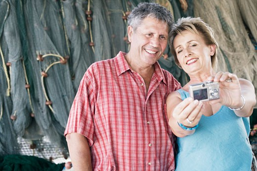 Stock Photo: 1491R-1157135 Close-up of a mature woman with a senior man taking a photograph of themselves