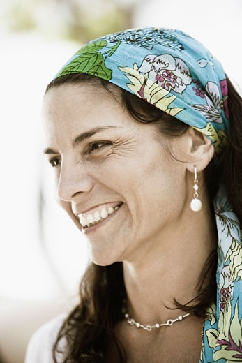 Close-up of a mid adult woman wearing a headscarf and smiling : Stock Photo