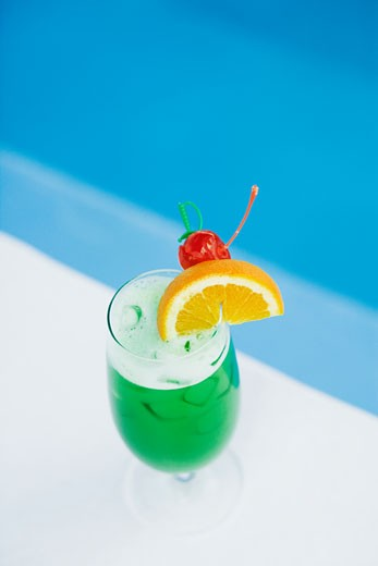 Stock Photo: 1491R-1157431 High angle view of a glass of cocktail at the poolside