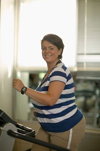 Overweight woman working out at gym : Stock Photo