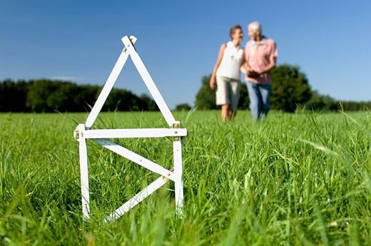 Couple standing behind miniature house in field, Swabian Alb, Baden-Wurttemberg, Germany : Stock Photo