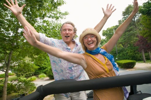 Stock Photo: 1491R-1158897 Mature man and a mid adult woman in a convertible car and smiling