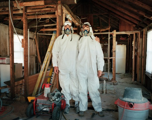 self portrait of my husband and me wearing hazmat suits after we gutted our house to renovate it. : Stock Photo