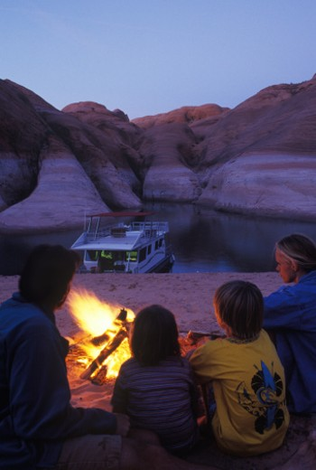 Family have campfire in desert, houseboat behind : Stock Photo
