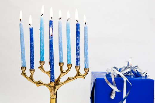 Stock Photo: 1491R-1159553 Lit candles in a menorah alongside a present wrapped in blue paper, commonly used during the Jewish celebration of Hanukkah.