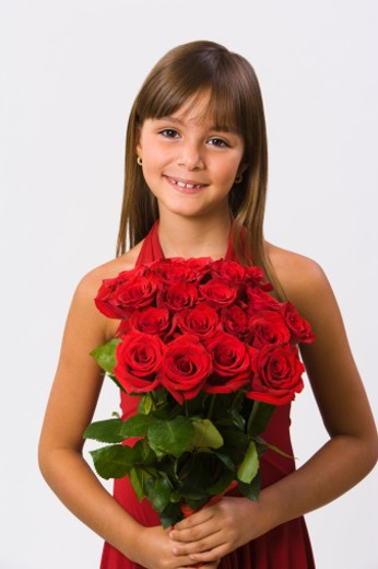Girl holding red roses, smiling, portrait : Stock Photo