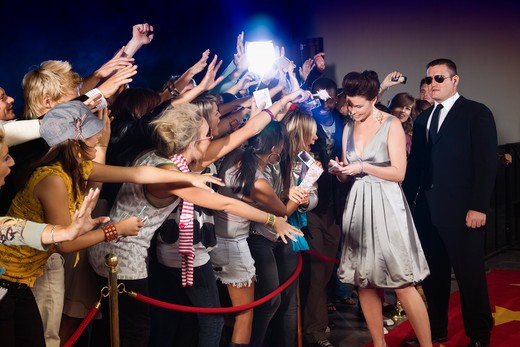 Celebrity signing autograph for screaming fans : Stock Photo