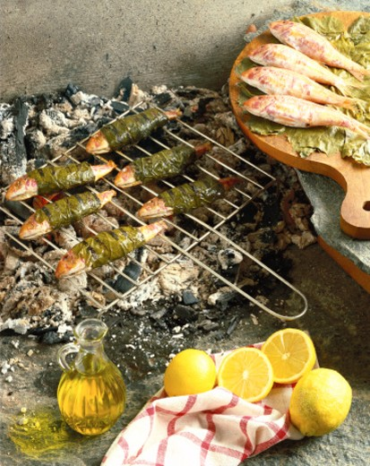 high angle view of leaf wrapped fish grilling on a coal fire beside lemons and olive oil : Stock Photo