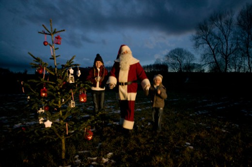 Children with Santa Claus looking at outdoor Christmas tree at night : Stock Photo