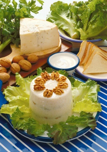 close-up of an appetizer garnished with walnuts with bread cheese and lettuce around it : Stock Photo