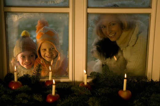 Stock Photo: 1491R-1160379 People looking at Christmas decorations of candles in apples near window
