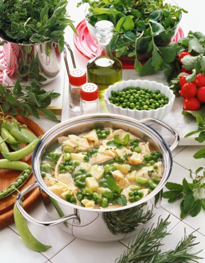 high angle view of a pot of soup with green peas served on a table with condiments and assorted herbs : Stock Photo