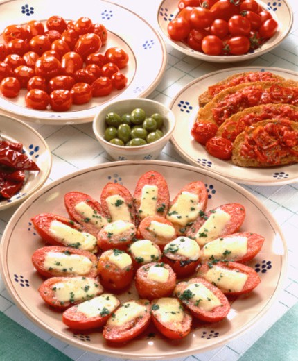close-up of cheese stuffed tomato appetizers served with olives and condiments : Stock Photo