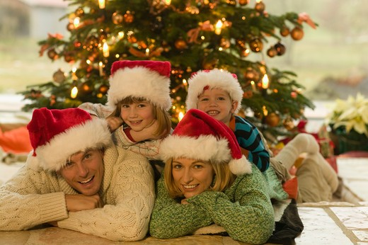 Family in santa hats laying near Christmas tree : Stock Photo