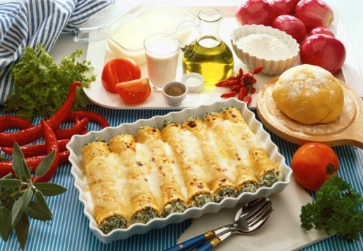high angle view of a baked dish topped with cheese served on a table with herbs and condiments : Stock Photo