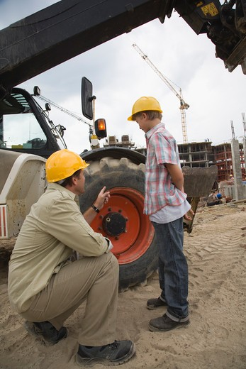 Stock Photo: 1491R-1160755 Foreman and boy looking at construction equipment