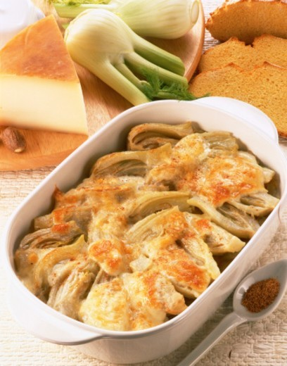 close-up of a baked dish topped with cheese served on a table with leeks and bread : Stock Photo