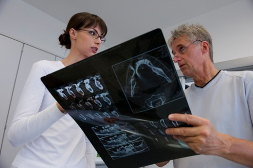 Stock Photo: 1491R-1161226 Dentist and hygienist reviewing x-ray