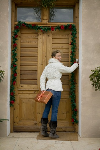 Stock Photo: 1491R-1161306 Woman with Christmas gift ringing doorbell