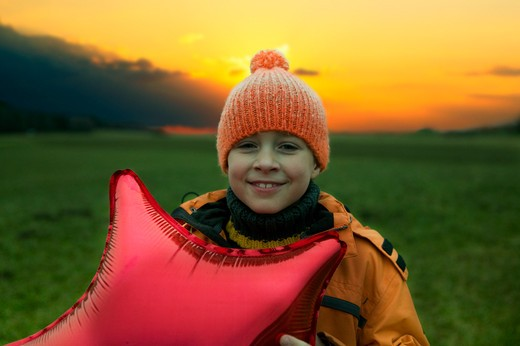 Stock Photo: 1491R-1161324 Boy holding balloon outdoors at sunset