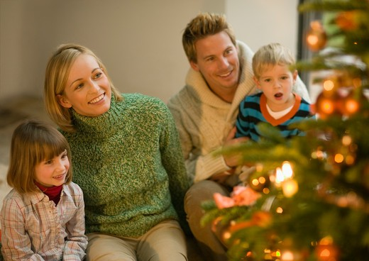 Family in living room looking at Christmas tree : Stock Photo