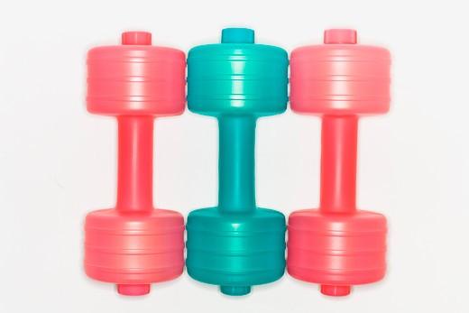 Stock Photo: 1491R-1161588 Color dumbbells form a line