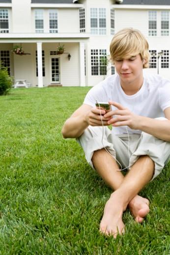 Teenage boy listening to music on lawn. : Stock Photo