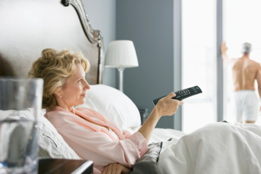 Woman in bed using television remote control. : Stock Photo