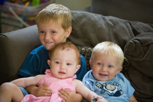 Stock Photo: 1491R-1163090 Three young children sitting together on a sofa.