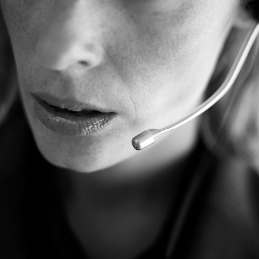 Close-up of a young businesswoman wearing a telephone headset : Stock Photo