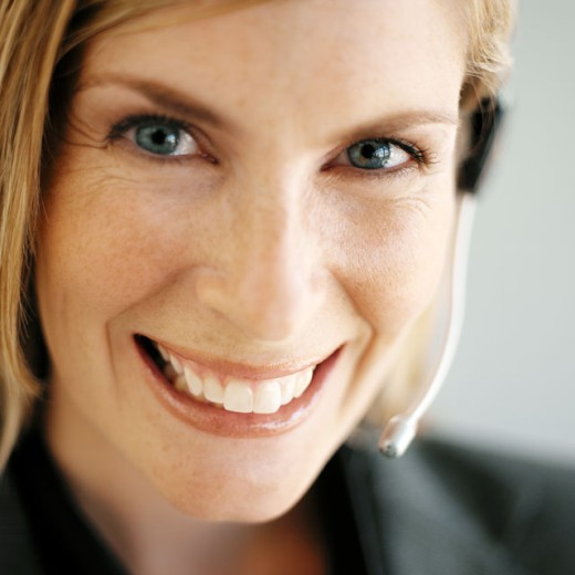 Portrait of a young businesswoman smiling wearing a telephone headset : Stock Photo
