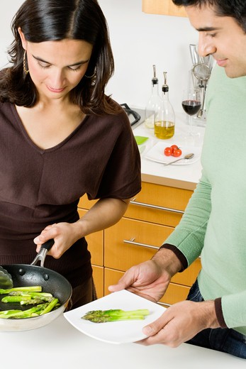 Woman dishing asparagus onto Man's plate. : Stock Photo