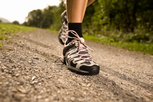Man walking in sports shoes on country path, low section : Stock Photo
