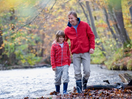 father and son walking by stream in autumn forest : Stock Photo
