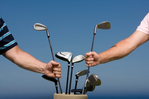 Stock Photo: 1491R-1164371 Mature men choosing golf clubs from golf bag, side view