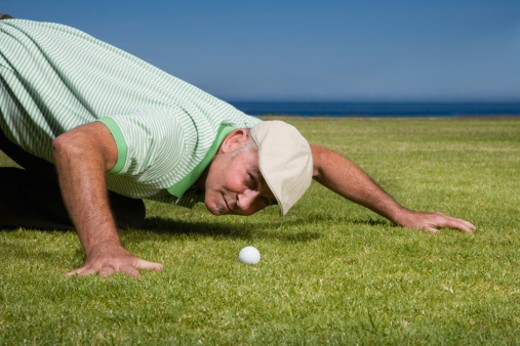 Mature man crouching on golf course, looking at golf ball : Stock Photo