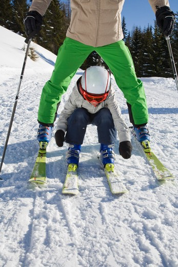 Young boy skiing through father's legs, low section : Stock Photo