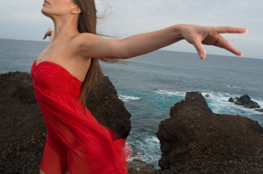 Stock Photo: 1491R-1164748 Young woman arms outstretched in red dress at rocks by sea