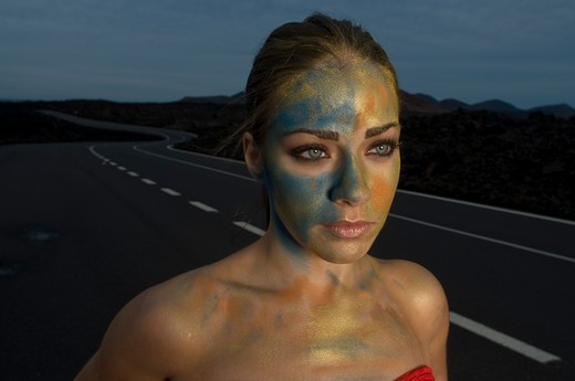 Young woman in body paint on empty road at night, close-up : Stock Photo